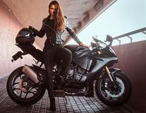 A seductive biker girl leaning on her superbike on a sidewalk inside the bridge on a sunny day. A seductive biker girl wearing black leather jacket leaning on royalty free stock photography
