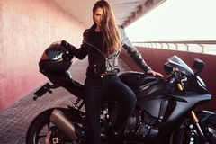 A seductive biker girl leaning on her superbike on a sidewalk inside the bridge on a sunny day. A seductive biker girl wearing black leather jacket leaning on stock photos