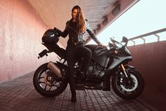 A seductive biker girl leaning on her superbike on a sidewalk inside the bridge on a sunny day. A seductive biker girl wearing black leather jacket leaning on royalty free stock photo