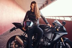 A seductive biker girl leaning on her superbike on a sidewalk inside the bridge on a sunny day. A seductive biker girl wearing black leather jacket leaning on stock photography
