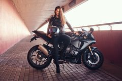 A seductive biker girl leaning on her superbike on a sidewalk inside the bridge on a sunny day. A seductive biker girl wearing black leather jacket leaning on stock image