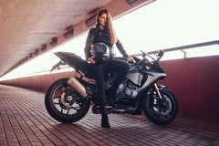 A seductive biker girl leaning on her superbike on a sidewalk inside the bridge on a sunny day. A seductive biker girl wearing black leather jacket leaning on royalty free stock image