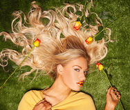Seductive blond with her hair covered in roses Royalty Free Stock Image