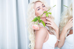 Seductive blond with a rose in her mouth Stock Image