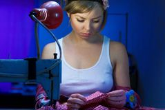 Seductive blond sewing in her workshop Stock Photo