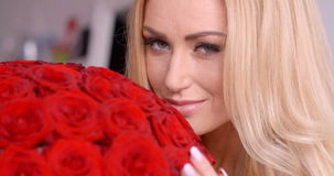 Seductive Blond Woman Behind Red Rose Bouquet stock video