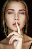 Seductive blonde with beautiful make-up. Pink shade, beauty portrait of a sexy girl who put a finger to his lips. A tender girl Stock Photography