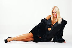 Seductive blonde in a black fur coat Stock Photos