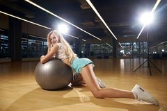 Seductive blonde female model posing leaning on silver balance ball Royalty Free Stock Photos