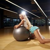 Seductive blonde female model posing leaning on silver balance ball Stock Photos