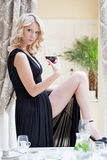 Seductive blonde posing with glass of wine Royalty Free Stock Image