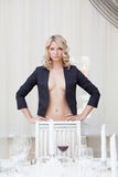 Seductive blonde posing topless in coat stock images