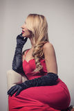 Seductive blonde woman in red dress sitting on chair Stock Image