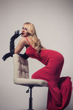 Seductive blonde woman in red dress sitting on chair Stock Images