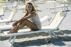 Seductive blonde woman sitting on a deck chair. Beautiful young blonde woman sitting on a deck chair at the beach in a sunny summer day Stock Photography
