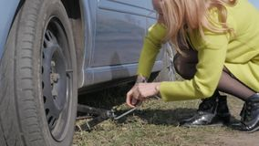 Seductive blonde woman trying change wheel on a car on rural road. 4K stock video footage