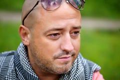 Seductive bold man wearing neck handkerchief resting outdoor Royalty Free Stock Photography