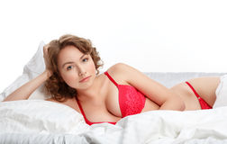 Seductive brunette beauty. Girl in red lingerie on the bed Stock Images
