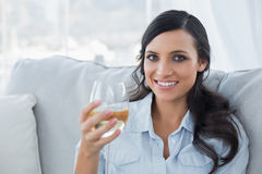 Seductive brunette drinking white wine on sofa Royalty Free Stock Image