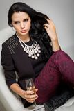 Seductive brunette holding a glass of champagne Stock Images