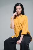 Seductive brunette model in yellow blouse sitting on stool,. Isolated on grey Stock Photo
