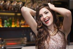 Seductive brunette posing for camera ruffling her hair. At the nightclub Stock Photo