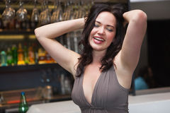 Seductive brunette posing for camera ruffling her hair. At the nightclub Royalty Free Stock Image