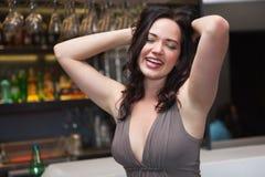 Seductive brunette posing for camera ruffling her hair Royalty Free Stock Image