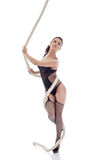 Seductive brunette posing hanging on rope Royalty Free Stock Photography