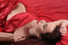 Seductive brunette in red satin Royalty Free Stock Photo