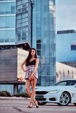 Seductive brunette woman dressed in modern clothes holds handbag posing near luxury car against a skyscraper. Seductive brunette woman dressed in modern clothes royalty free stock photos