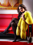 Seductive brunette woman posing at red leather sofa on yellow fur accessory. Stock Photography