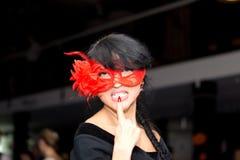 Seductive brunette woman wearing a Venetian mask. Nonconformist seductive mysterious brunette woman wearing a red Venetian masquerade eye mask, looking at camera royalty free stock images