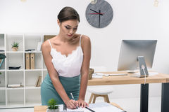 Seductive businesswoman writing in notebook at modern office Royalty Free Stock Photography