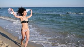 Seductive female with curly hair resting on tropical island, Young beautiful girl running along beach, happy woman. With developing hair and cloth in hands near stock footage