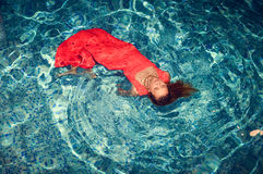 Seductive female floating on swimming pool in Stock Image