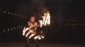 Woman spinning burning fans during fireshow at dusk. Seductive firegirl performing amazing art of spinning fire fans near river, gleams of fire illuminating stock footage