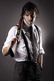 Seductive gangster with shotgun. Handsome fashion model dressed like a gangster posing with shotgun. Grey backdrop portrait royalty free stock photography