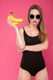 Seductive girl in sunglasses holding bananas and showing her tongue Royalty Free Stock Images