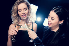 Seductive glamour multiethnic girls toasting with champagne glasses and spending time at party. Smiling seductive glamour multiethnic girls toasting with Royalty Free Stock Image