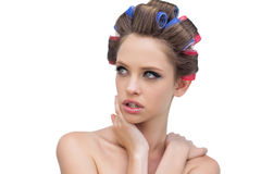 Seductive lady in hair rollers posing and looking away. Seductive young lady in hair rollers posing and looking away on white background Royalty Free Stock Image
