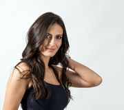 Seductive Latino beauty with hand holding her dark healthy wavy hair Stock Photography