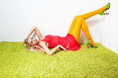 Seductive laying gorgeous sexy woman on green rug Stock Image
