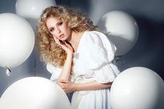 Seductive model in a white dress with balloons. Fashion. Royalty Free Stock Photography