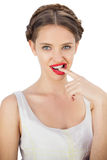 Seductive model in white dress posing with a finger in her mouth Royalty Free Stock Photos