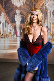 Seductive natural blond model posing sexy, wearing red lingerie and blue fur coat and showing her best body parts Stock Photo