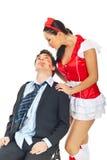 Seductive nurse with kissed businessman stock photography