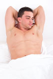 Seductive pensive man lying in bed with naked torso Royalty Free Stock Photography