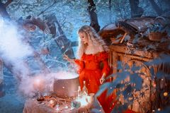 The seductive queen in a red dress with bare shoulders of the Baroque epoch, prepares poison for her enemies, late at. Night in an abandoned house. Gorgeous royalty free stock images