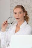 Seductive secretary. Holding glasses to her face Royalty Free Stock Photo